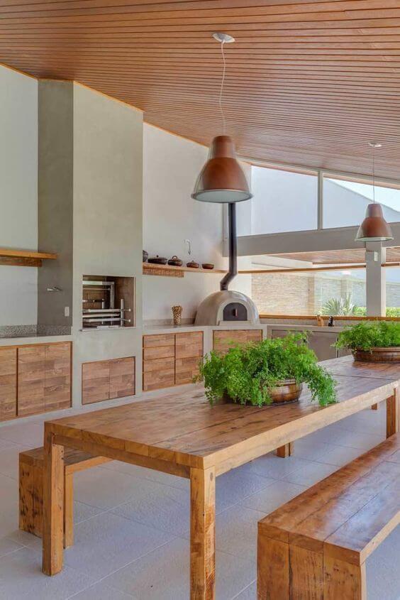 Área gourmet com churrasqueira pequena e moveis de madeira na decoração