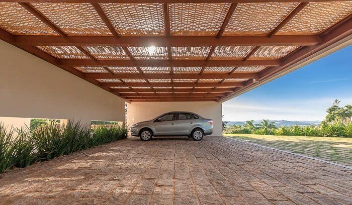 A cobertura de madeira para garagem com acabamento em tela chama a atenção no imóvel. Fonte: Pinterest