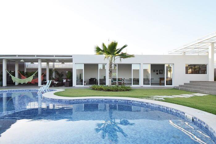 A grama natural acompanha o design da piscina grande. Projeto de A.M Studio Arquitetura