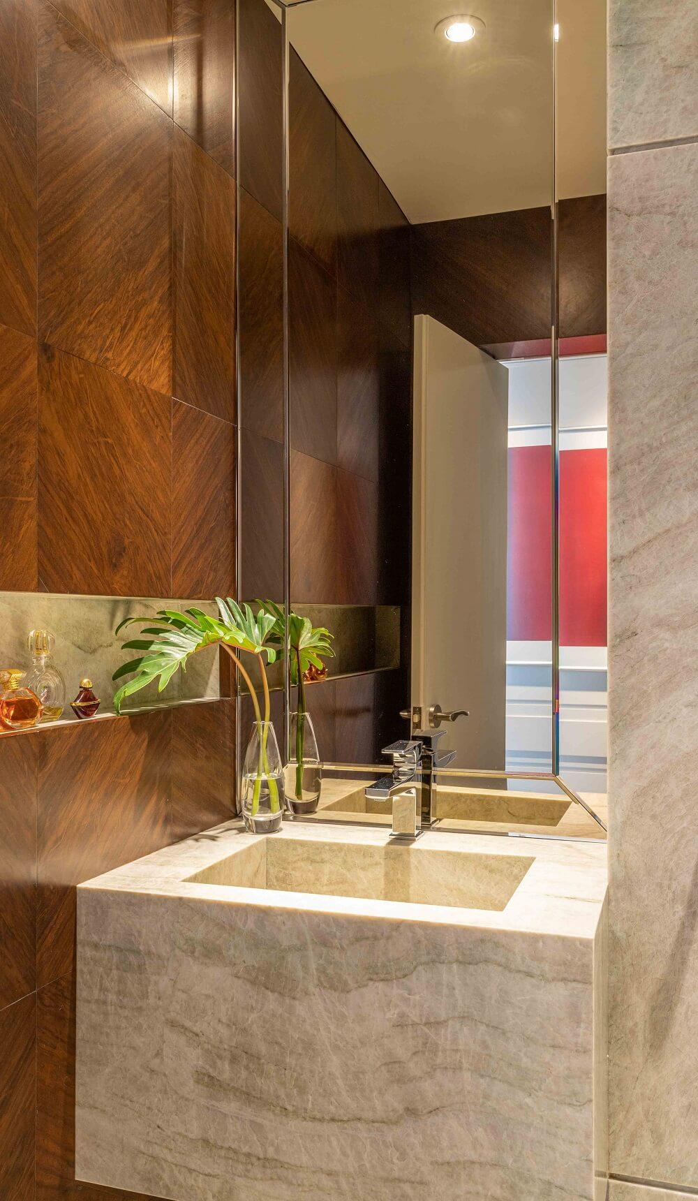 A parede do lavabo é marcada pela presença de um painel em lâmina natural de madeira. Foto: Leandro Moraes