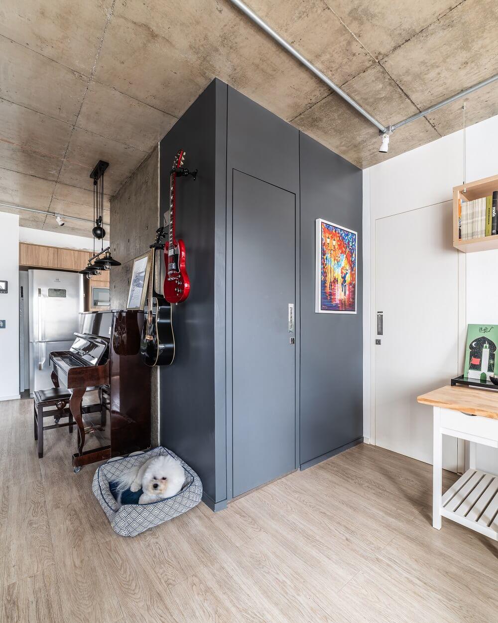 A parede preta camufla a porta que leva ao lavabo e se conecta com o estilo industrial. Foto: Guilherme Pucci
