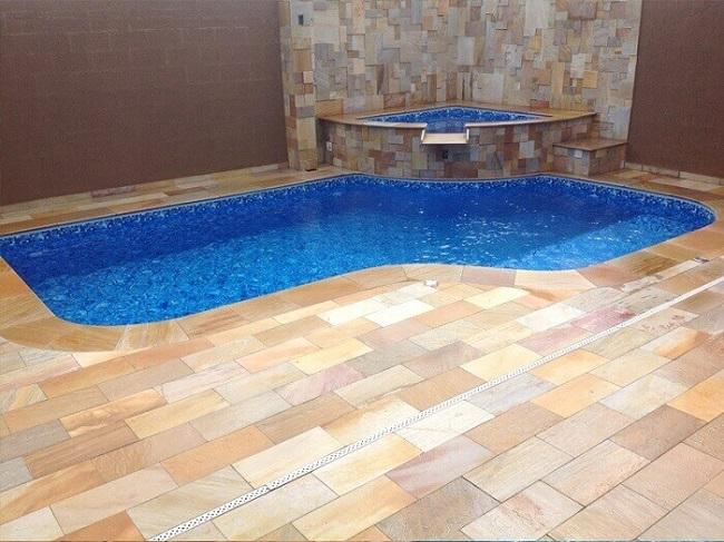 A pedra São Tomé usada como revestimento externo de piso na área da piscina. Fonte: Pinterest