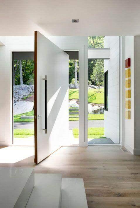A porta pivotante branca é perfeita para decorar a entrada de casa