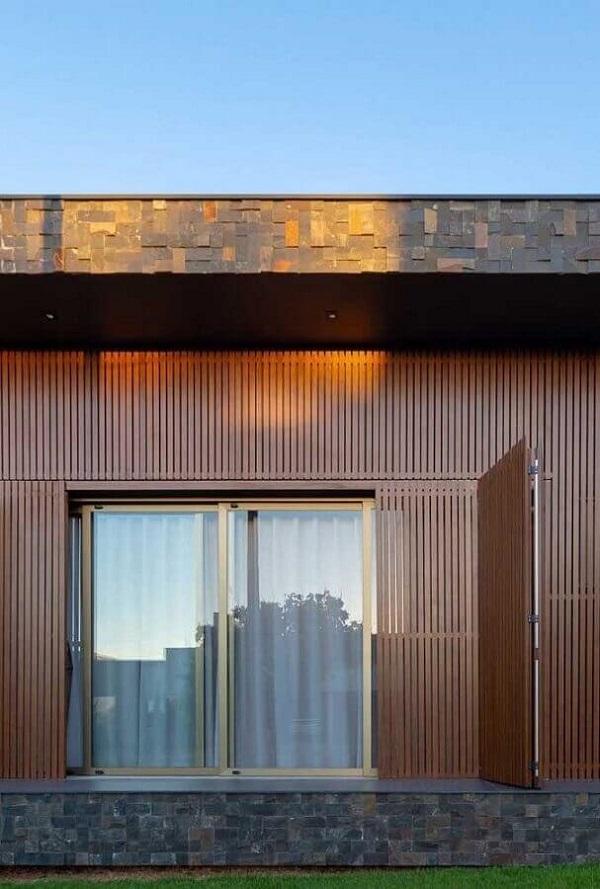 Alguns projetos de casas com revestimento externo em pedra ferro mesclam com outros tipos de madeira. Fonte: Pinterest