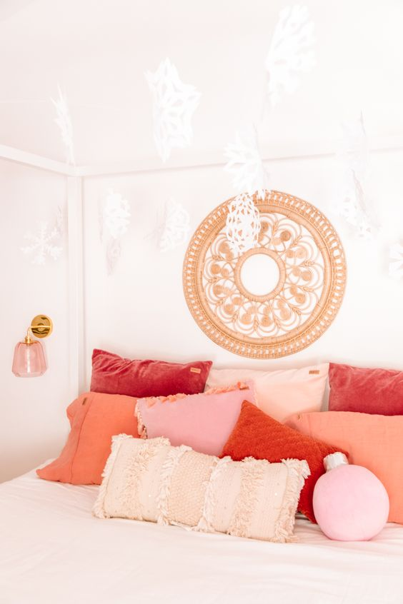 Almofadas cor pêssego e coral no quarto branco