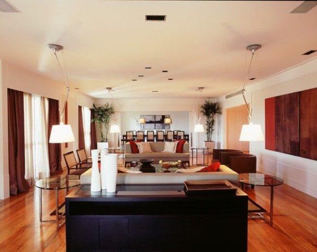 Aparador de madeira preto e mesas de vidro decoram a sala de estar. Projeto de Fernando Piva