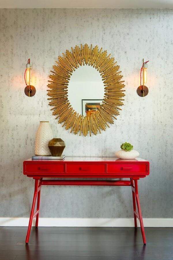 Aparador para sala pé palito vermelho e espelho dourado decoram o espaço. Fonte: Pinterest