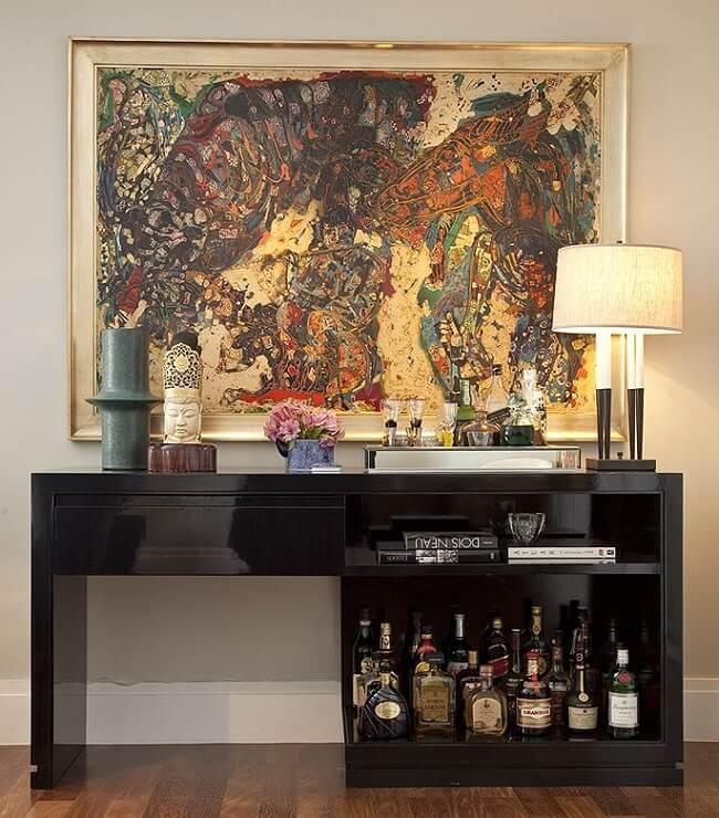 Aparador preto laqueado assume a função de bar na sala de estar. Projeto de Fernando Piva