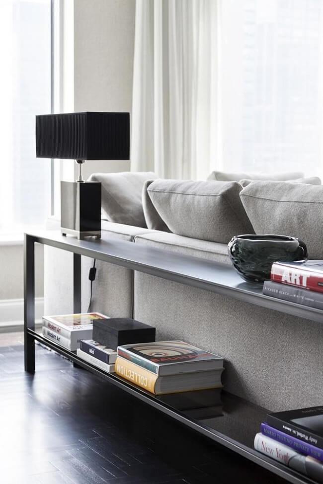 Aparador preto para sala decorado com abajur e livros. Projeto de Roberto Migotto