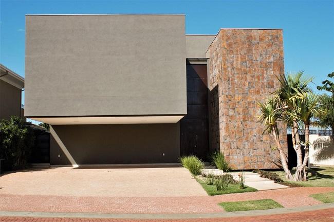 Arquitetura moderna com revestimento externo em pedra ferro. Projeto de Bezzon Arquitetura