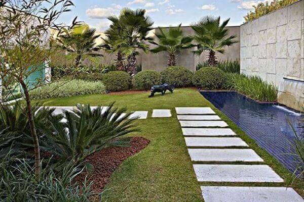 As placas de mármore do jardim formam o caminho da área externa. Projeto de Glaucia Britto