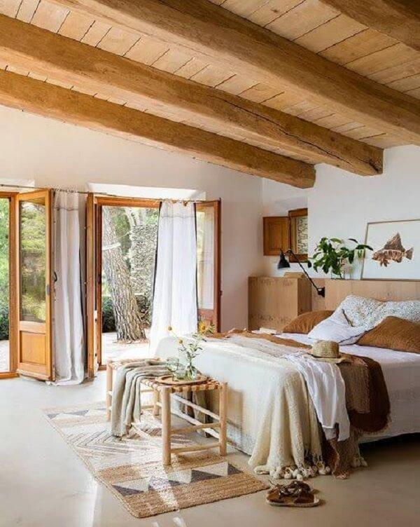As toras do teto aparente deixam o quarto marrom ainda mais rústico. Fonte: Casa Tres Chic