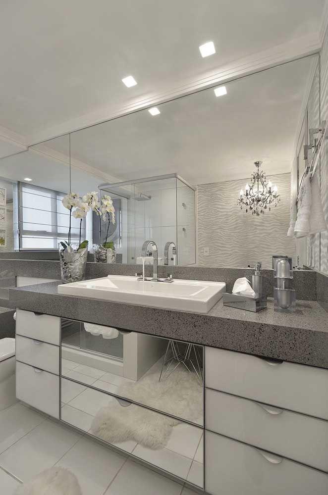 Banheiro com granito cinza e gabinete espelhado