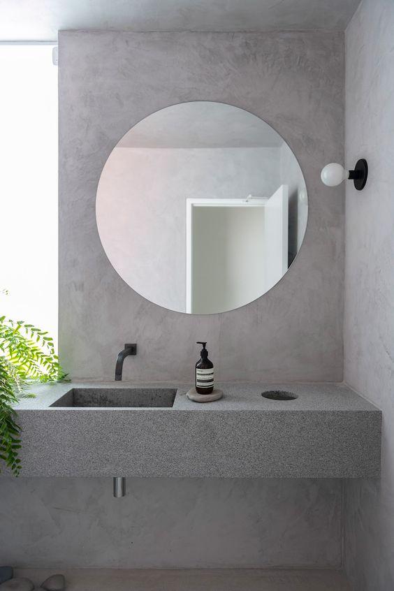 Banheiro com pia de granito cinza e espelho redondo