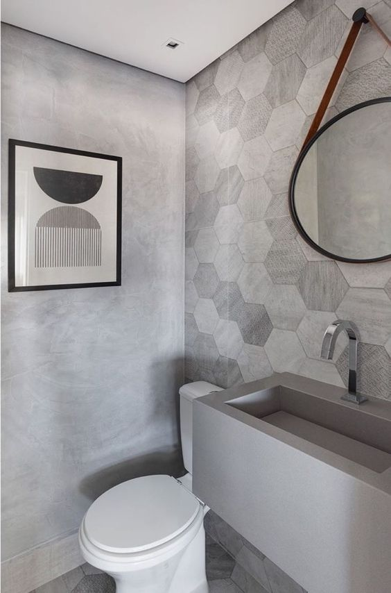 Banheiro com pia de granito cinza esculpida e decoração moderna