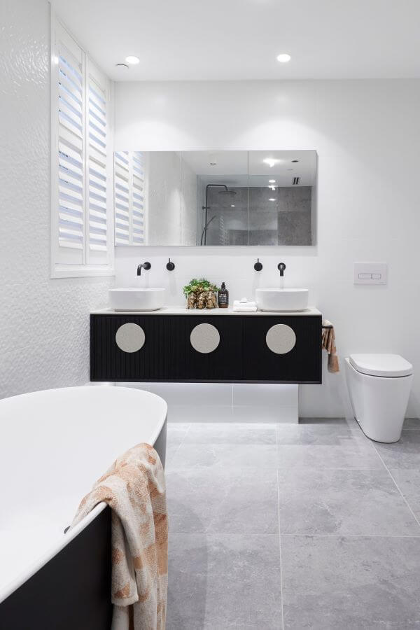 Banheiro com piso de cimento queimado com banheira preta