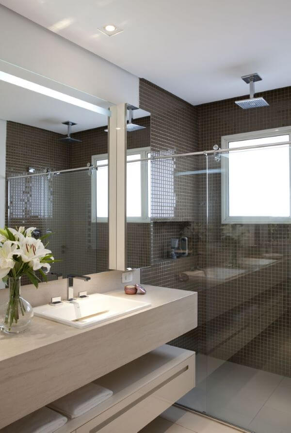 Banheiro com revestimentos em tons de marrom e pedra da pia bege