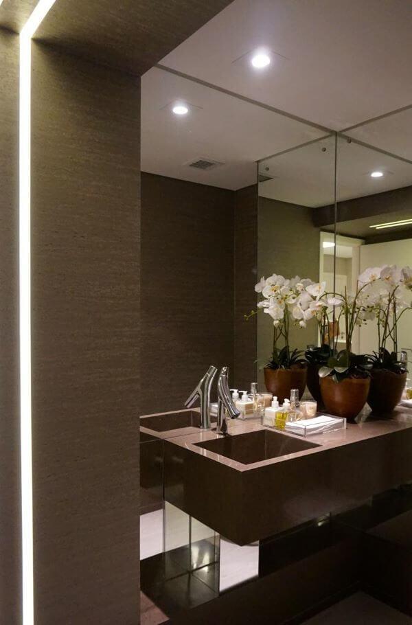 Banheiro decorado com tons de marrom e vaso de orquidea