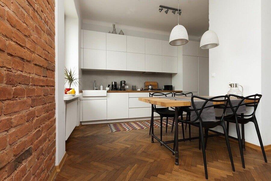 Cadeiras pretas e piso de madeira para decoração de cozinha branca planejada Foto Habitissimo