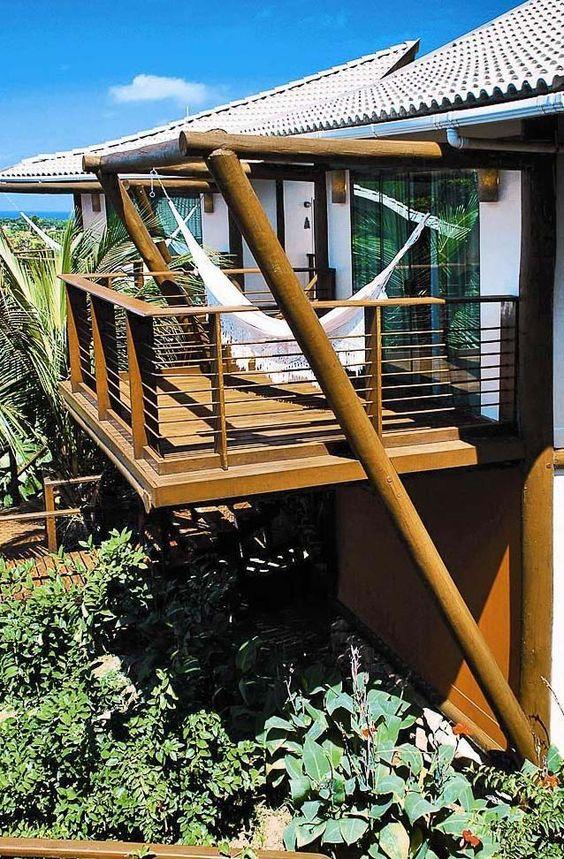Casa de madeira com sacada e rede de descanso