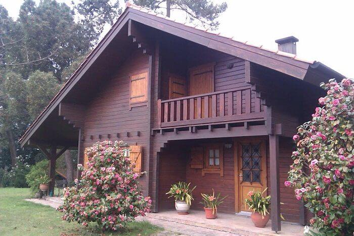 Casa de madeira com sacada e flores na decoração
