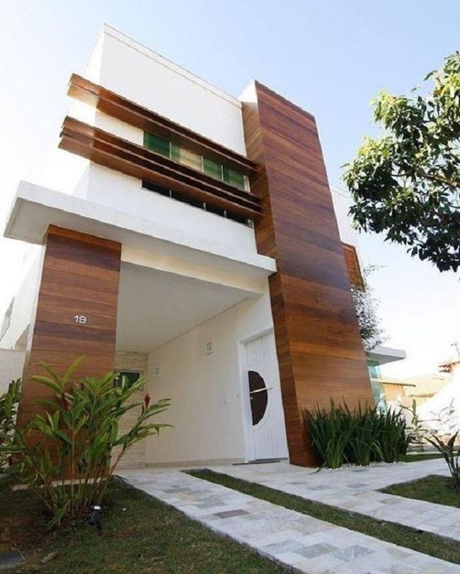 Casa moderna com revestimento externo em madeira e canteiro com arbustos. Fonte: Revista Viva Decora