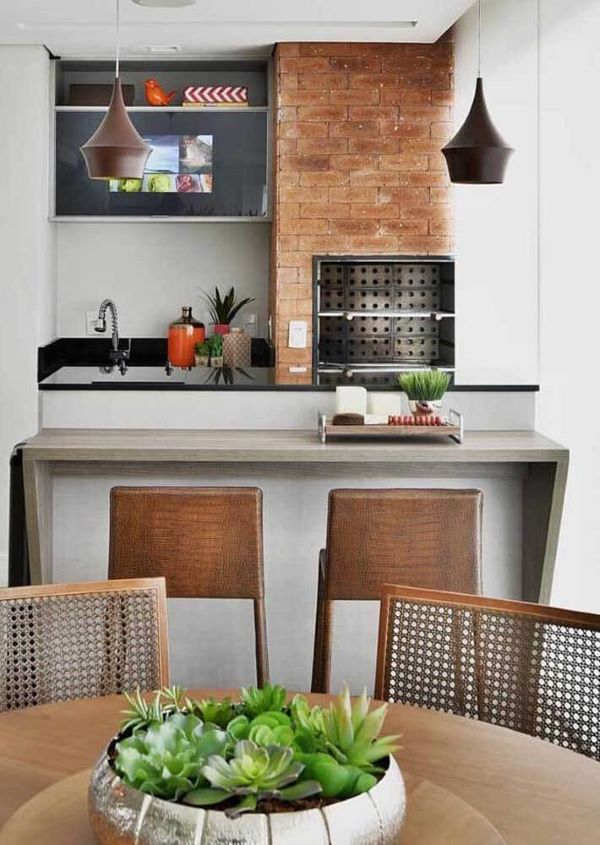Churrasqueira de tijolinho pequena na área gourmet de apartamento