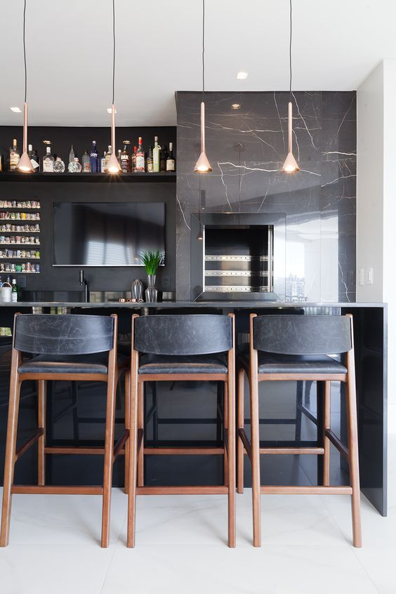 Churrasqueira gourmet de parede com revestimento marmorizado e bancada de granito preta para banquetas