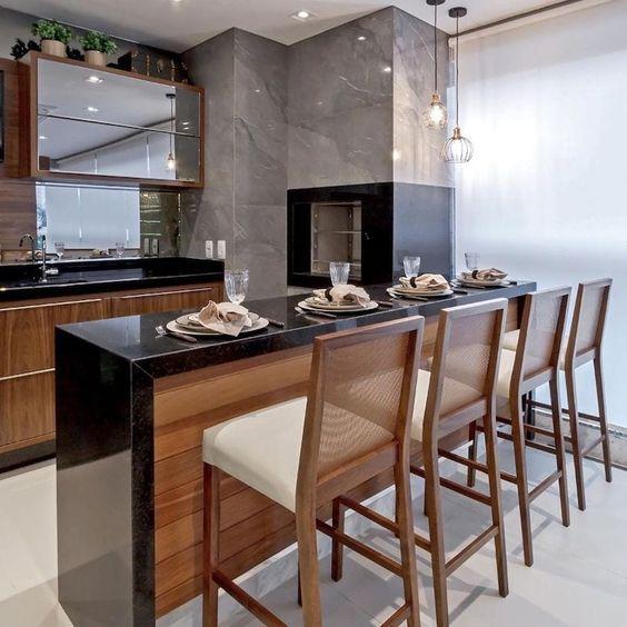 Churrasqueira gourmet de parede da cozinha com bancada de granito preta no ambiente moderno