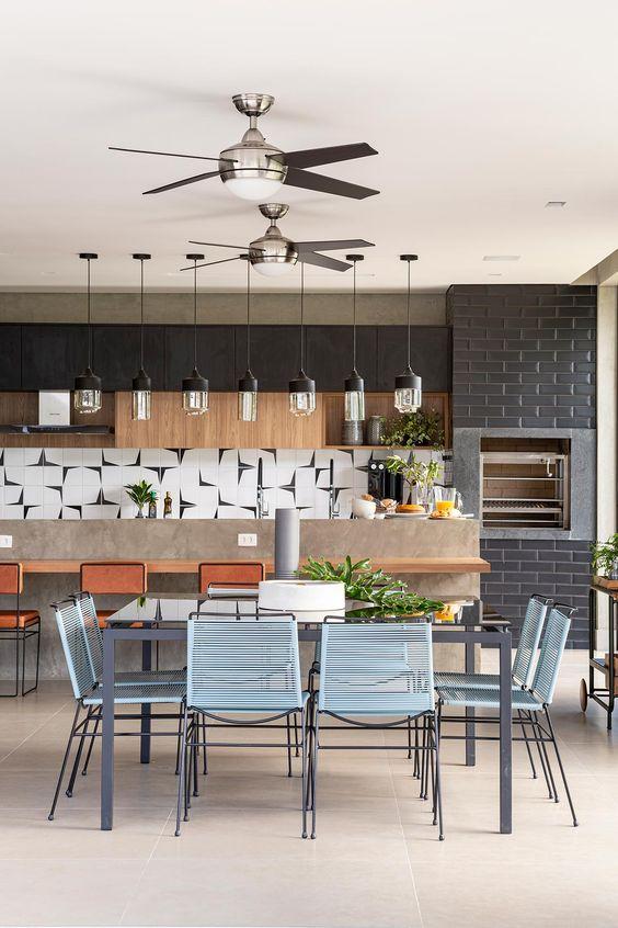 Churrasqueira gourmet de parede e inox com mesa de jantar moderna e cadeiras azuis