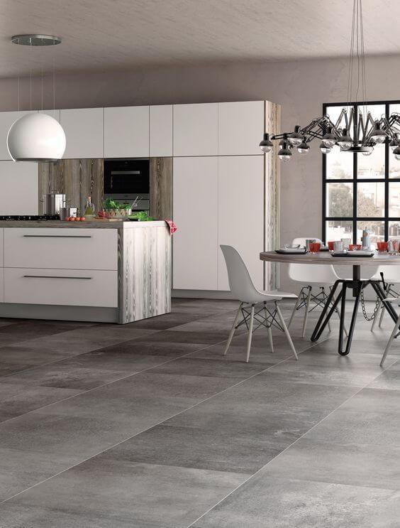 Cozinha americana com piso de porcelanato cimento queimado e armários brancos