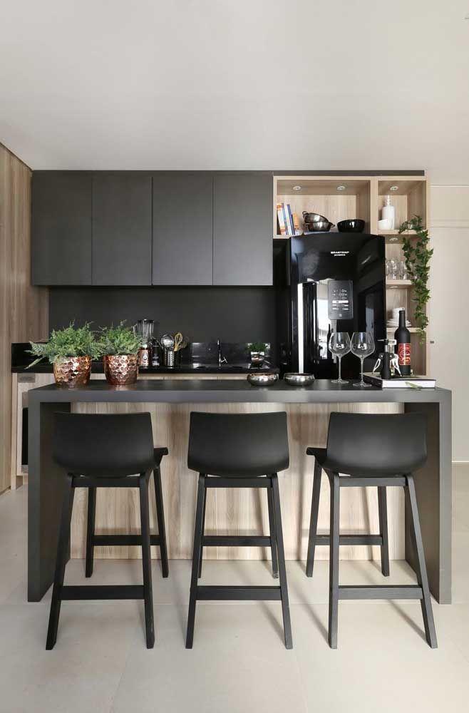 Cozinha com bancada de granito cinza e banqueta preta