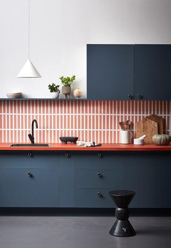 Cozinha com revestimento na cor pêssego e armários azuis