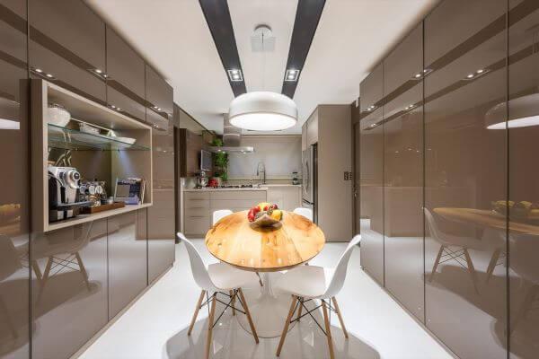 Cozinha em tons de marrom e mesa redonda pequena