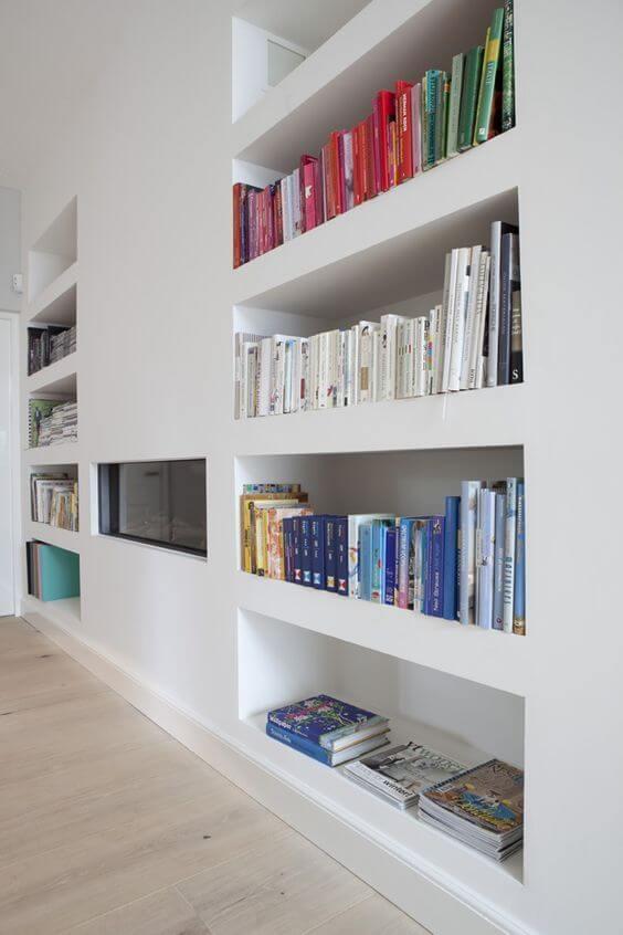 Decoração com estante de gesso com livros e lareira elétrica