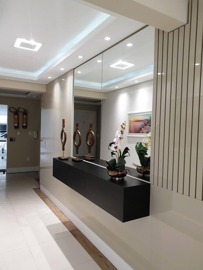 Decoração de hall de entrada com aparador suspenso preto. Projeto de Larissa Minatti
