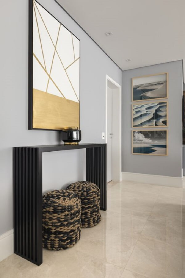 Decoração de sala de estar com aparador preto pequeno. Projeto de Rogério Galli