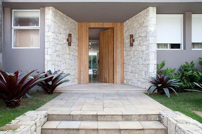 Entrada sofisticada com revestimento externo em pedras. Projeto de CSDA Arquitetura + Decoração