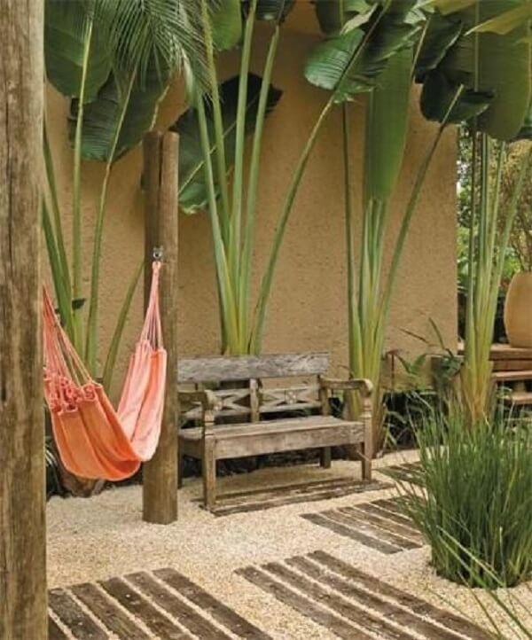 Espaço aconchegante com rede de descanso, banco d emadeira e jardim com pedras rústicas. Fonte: Pinterest