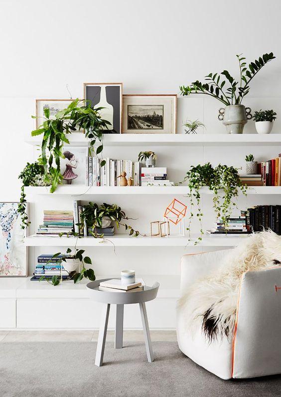 Estante de gesso para sala de estar clean decorada com vasos e quadros