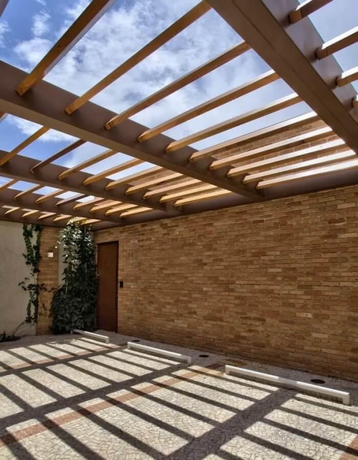 Fachada com parede de tijolinho e cobertura de madeira para garagem. Fonte: Revista Viva Decora