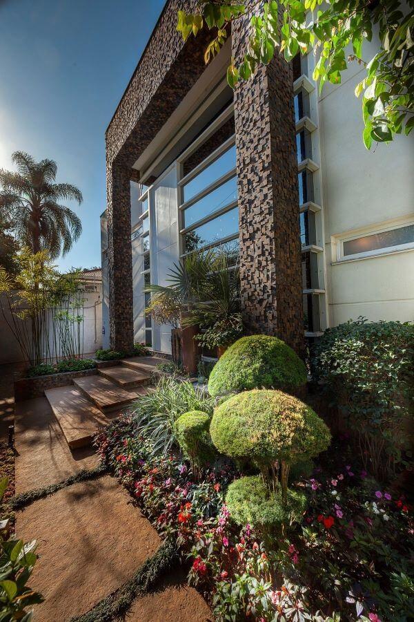 Fachada de casa com janelas de vidro e revestimento 3D externo. Projeto de Aline Cobra Design Arquitetura