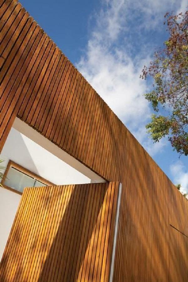 Fachada rústica com revestimento externo de madeira. Projeto de Francisco Calio
