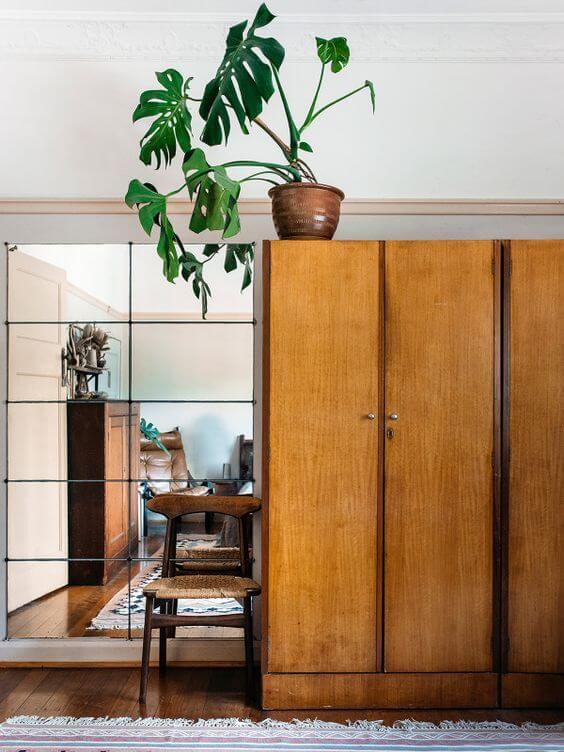 Guarda roupa rustico de madeira no quarto com espelho