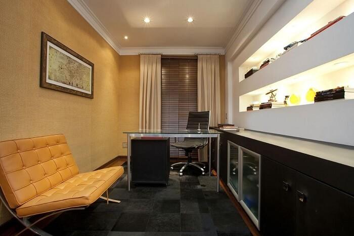 Home office com gaveteiro preto posicionado embaixo da mesa de vidro. Projeto de Deborah Basso