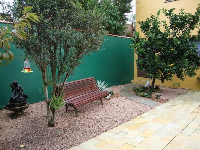 Jardim com pedras rústicas e árvores frutíferas decoram a área externa. Projeto de Juliana Litwinski