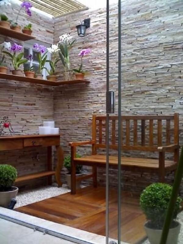 Jardim simples com pedras brancas e prateleiras com orquídeas. Fonte: Pinterest