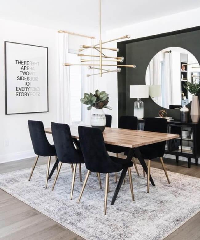 Lustre pendente, piso laminado e aparador pé palito preto decoram a sala de jantar. Fonte: Revista Viva Decora 2