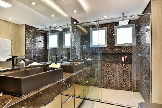 Banheiro com tons de marrom no revestimento e pedra de granito