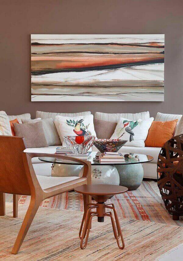 Sala de estar com parede marrom acinzentado e almofadas alaranjadas